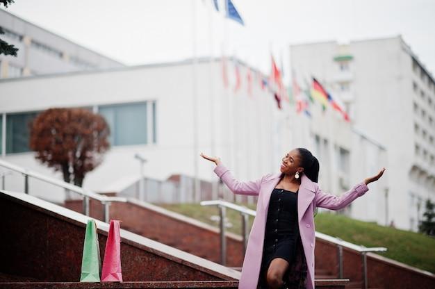 世界のさまざまな国の国旗に対して、ファッションの服装のコートを着ている通りで若いスタイリッシュな美しいアフリカ系アメリカ人女性。