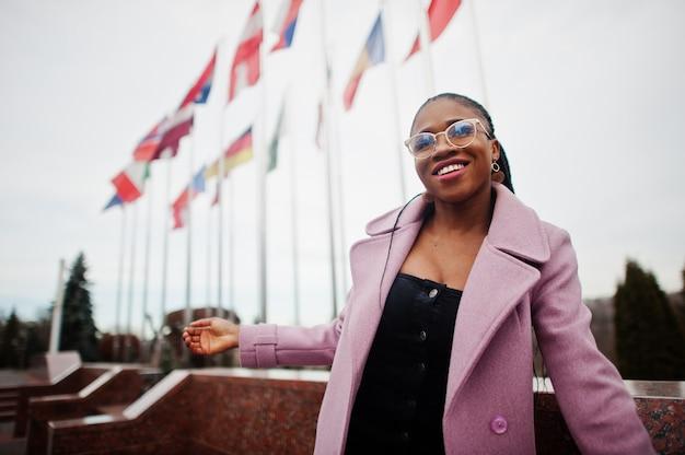 世界のさまざまな国の国旗に対して、ファッション衣装のコートと眼鏡を身に着けている通りで若いスタイリッシュな美しいアフリカ系アメリカ人女性。
