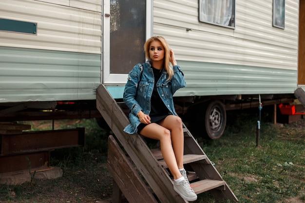 트레일러 차 근처에 앉아 청바지 재킷과 신발에 젊은 세련된 아름다운 미국 여자