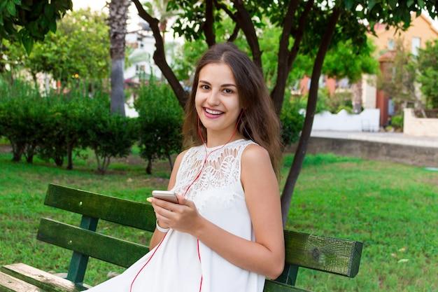 세련 된 아름 다운 소녀는 휴대 전화에 헤드폰으로 음악을 듣고 즐긴다
