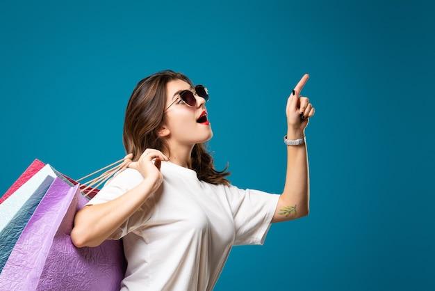 Молодая стильная красивая девушка в солнечных очках гуляет с разноцветной сумкой для покупок