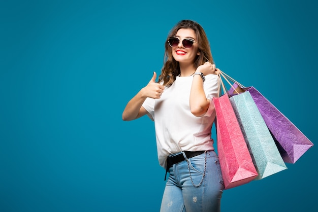 Молодая стильная красивая девушка в солнцезащитных очках ходит с разноцветными сумками для покупок
