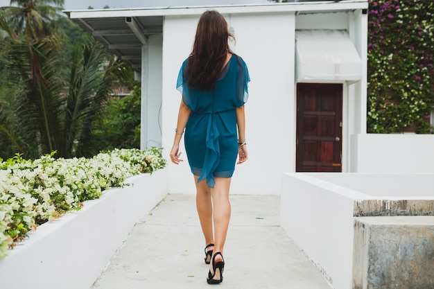 Young stylish beautiful woman in blue dress, summer fashion trend, vacation, garden, tropical hotel terrace, smiling, walking