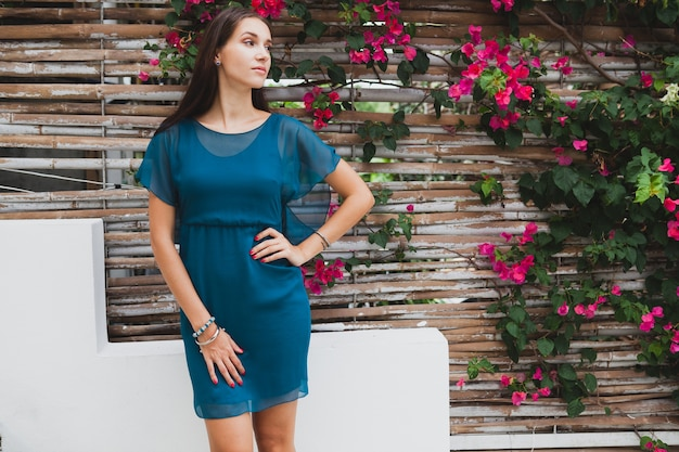 Young stylish beautiful woman in blue dress, summer fashion trend, vacation, garden, tropical hotel terrace, smiling