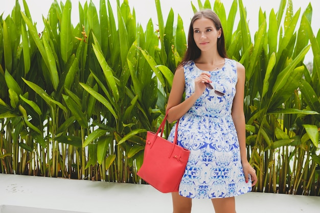 Giovane bella donna elegante in abito blu stampato, borsa rossa, occhiali da sole, vestito alla moda, abbigliamento alla moda, sorridente, seduta, estate, accessori