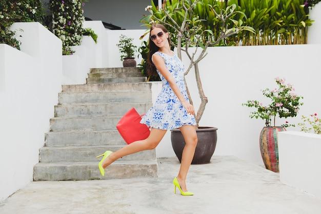 Giovane bella donna elegante in abito blu stampato, borsa rossa, occhiali da sole, buon umore, vestito di moda, abbigliamento alla moda, sorridente, estate, accessori, giocoso, camminare, correre su scarpe gialle tacco alto
