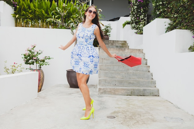 Young stylish beautiful woman in blue printed dress, red bag, sunglasses, happy mood, fashion outfit, trendy apparel, smiling, summer, accessories, playful, walking, running on high heel yellow shoes