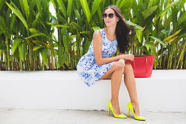 Young stylish beautiful woman in blue printed dress, red bag, sunglasses, happy mood, fashionable outfit, trendy apparel, smiling, sitting, summer, yellow high heel shoes, accessories