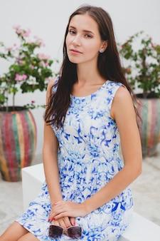 Giovane bella donna alla moda in abito blu stampato, occhiali da sole, buon umore, vestito di moda, abbigliamento alla moda, sorridente, estate, accessori