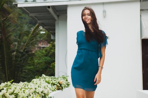 Молодая стильная красивая женщина в синем платье, летняя мода, отдых, сад, тропическая терраса отеля, улыбка, прогулки