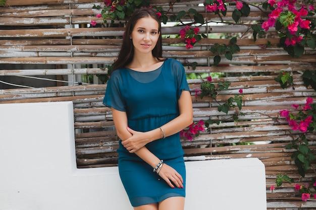 Молодая стильная красивая женщина в синем платье, летняя мода, отдых, сад, терраса тропического отеля, улыбается