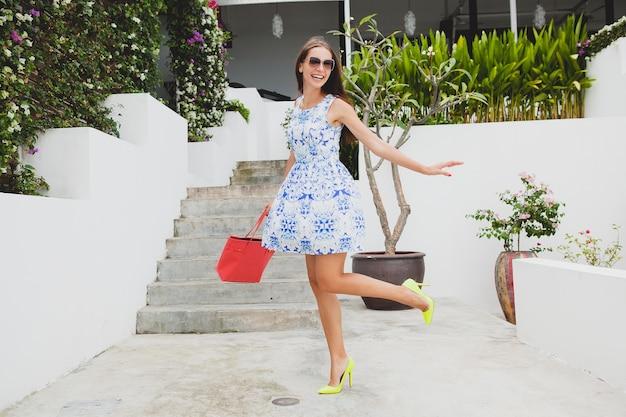青いプリントドレス、赤いバッグ、サングラス、幸せな気分、ファッション衣装、流行のアパレル、笑顔、夏、アクセサリー、遊び心、ウォーキング、ハイヒールの黄色い靴で走っている若いスタイリッシュな美しい女性