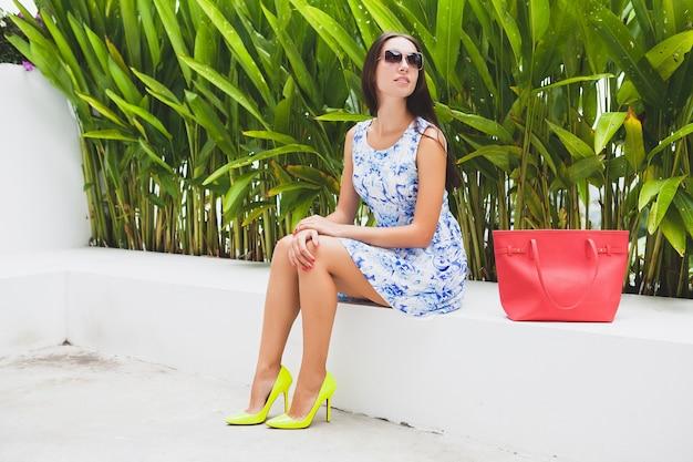 青いプリントドレス、赤いバッグ、サングラス、幸せな気分、ファッショナブルな服装、トレンディなアパレル、笑顔、座っている、夏、黄色のハイヒールの靴、アクセサリーの若いスタイリッシュな美しい女性
