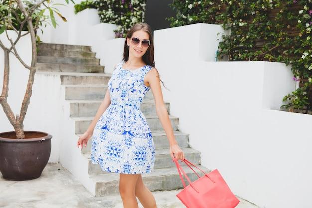 青いプリントドレス、赤いバッグ、サングラス、幸せな気分、ファッショナブルな服装、流行のアパレル、笑顔、夏、アクセサリーの若いスタイリッシュな美しい女性