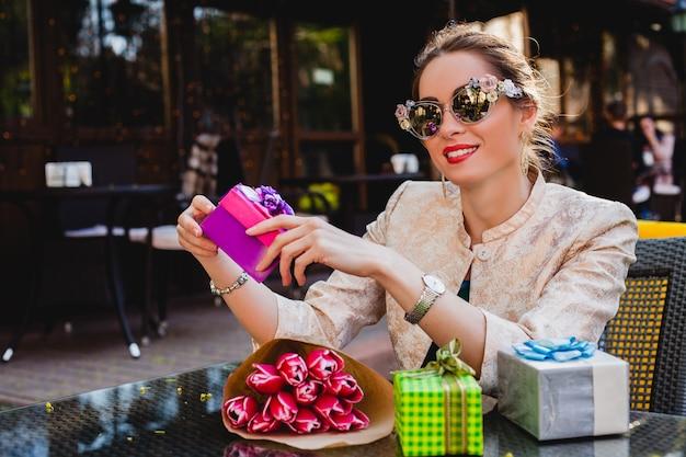 Молодая стильная красивая женщина в модных солнцезащитных очках, сидя в кафе