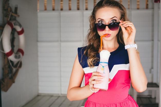 바다 카페에서 젊은 세련된 아름다운 여자, 칵테일 스무디, 선글라스, 유혹, 리조트 스타일, 유행 복장, 미소, 해양 색상 드레스, 앵커 및 배경에 구명 부표, 충격