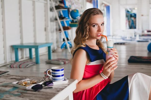海のカフェで若いスタイリッシュな美しい女性、カクテルスムージー、サングラス、軽薄、リゾートスタイル、ファッショナブルな服装、笑顔、マリンカラーのドレスを飲む