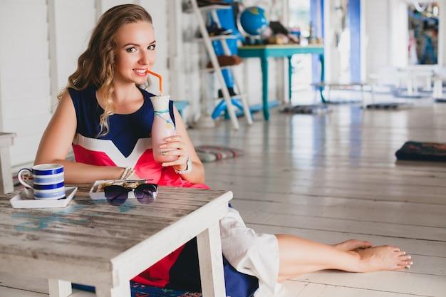 바다 카페에서 젊은 세련된 아름다운 여자, 칵테일 스무디, 선글라스, 유혹, 리조트 스타일, 유행 복장, 미소, 해양 색상 드레스를 마시는
