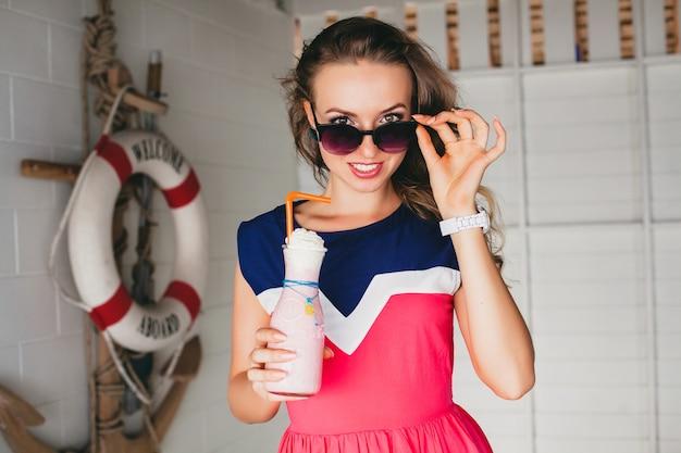 Giovane bella donna elegante in caffè sul mare, bere frullato cocktail, occhiali da sole, flirty, stile resort, vestito alla moda, sorridente, vestito dai colori marini, ancora e salvagente sullo sfondo, scioccato