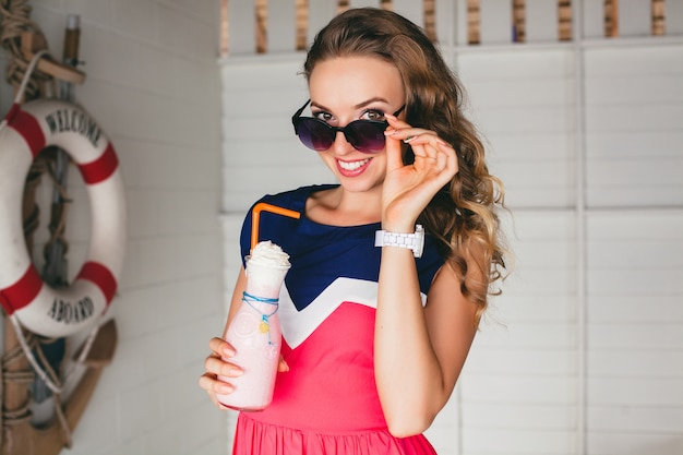 Young stylish beautiful woman in sea cafe, drinking cocktail smoothie, sunglasses, flirty, resort style, fashionable outfit, smiling, marine colors dress, anchor and lifebuoy on background, shocked