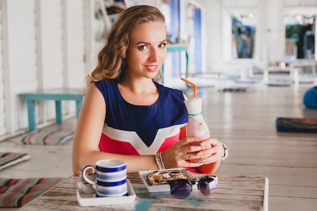 Giovane bella donna elegante in caffè sul mare, bere frullato cocktail, occhiali da sole, flirty, stile resort, vestito alla moda, sorridente, vestito dai colori marini