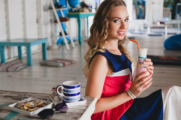 Young stylish beautiful woman in sea cafe, drinking cocktail smoothie, sunglasses, flirty, resort style, fashionable outfit, smiling, marine colors dress