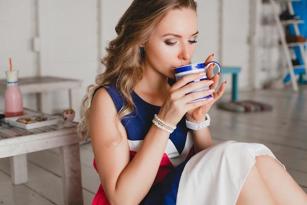 Giovane bella donna elegante in caffè sul mare, bere cappuccino caldo, stile resort, vestito alla moda, sorridente, vestito dai colori marini, seduto sul pavimento, vacanza, relax