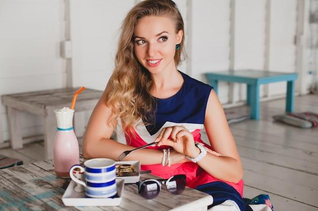 Giovane bella donna alla moda in caffè sul mare, mangiare frittelle, frullato cocktail, occhiali da sole, flirty, stile resort, vestito alla moda, sorridente, vestito dai colori marini