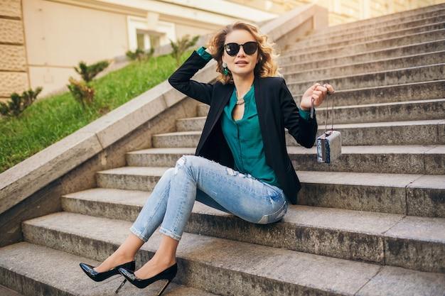 청바지, 검은 색 재킷, 녹색 블라우스, 선글라스를 착용하고 거리에 앉아 젊은 세련된 아름다운 여자