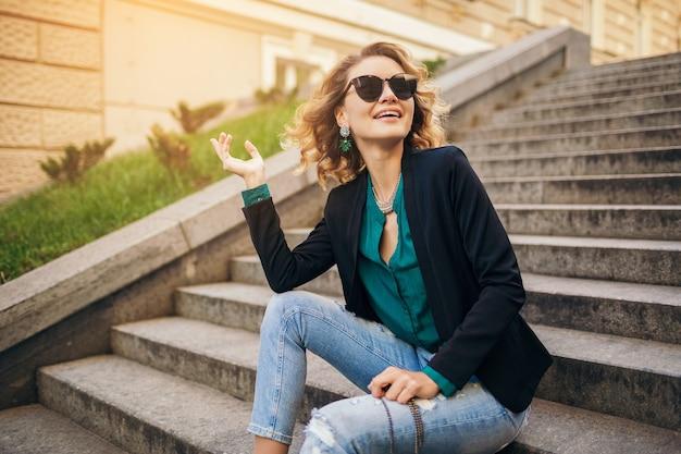 청바지, 검은 재킷, 녹색 블라우스, 선글라스를 착용하고, 지갑, 우아한 스타일, 여름 패션 트렌드를 들고 도시 거리의 계단에 앉아 젊은 세련된 아름다운 여자, 웃고