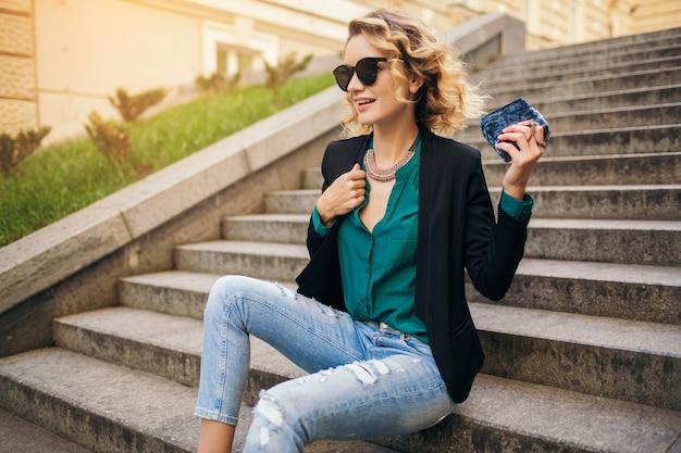 街の通りの階段に座って、ジーンズ、黒のジャケット、緑のブラウス、サングラス、財布を持って、エレガントなスタイル、夏のファッショントレンド、笑顔の若いスタイリッシュな美しい女性