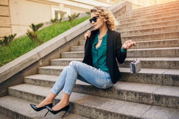 Giovane bella donna alla moda seduta in strada, indossa jeans, giacca nera, camicetta verde, occhiali da sole