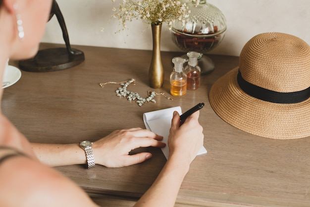 Young stylish beautiful woman sitting at table in resort hotel room, writing a letter, holding pen, straw hat, vintage style, hands close-up, details, accessories, travel diary