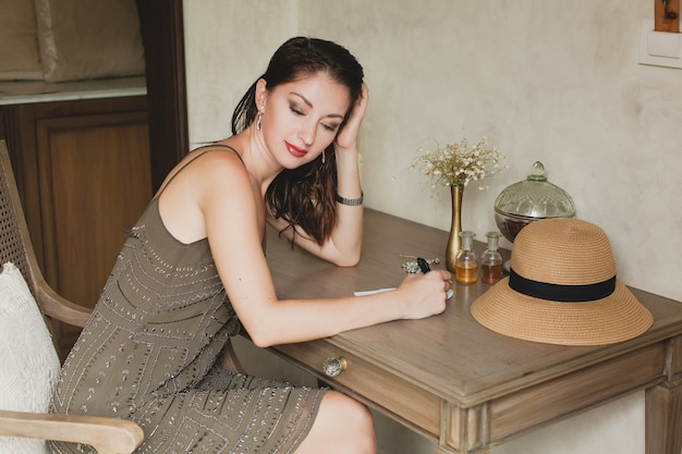 Young stylish beautiful woman sitting at table in resort hotel room, writing a letter, thinking, sophisticated, smiling, happy, bohemian outfit, holding pen, straw hat, vintage style