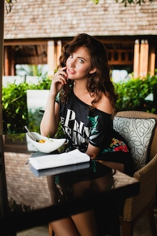 Young stylish beautiful woman sitting at tropical resort cafe, smiling