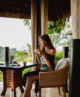 Young stylish beautiful woman sitting at tropical resort cafe
