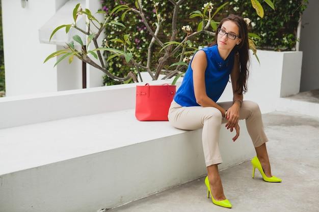 Молодая стильная красивая женщина, тренд летней моды, синяя блузка, красная сумка, очки, тропический курорт вилл, отпуск, кокетливая, длинные стройные ноги, брюки, желтые туфли, каблуки