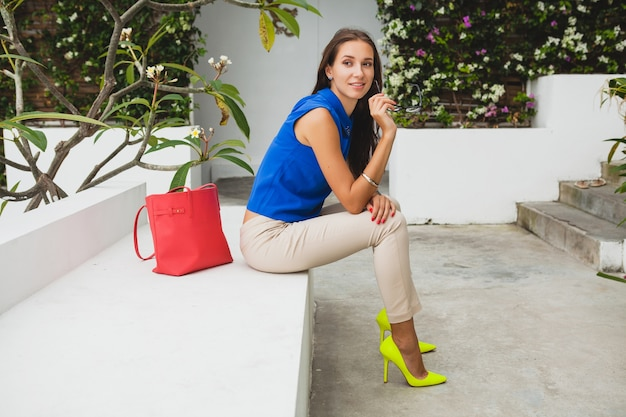 Young stylish beautiful woman, summer fashion trend, blue blouse, red bag, glasses, tropical villa resort, vacation, flirty, long slim legs, trousers, yellow shoes, heels