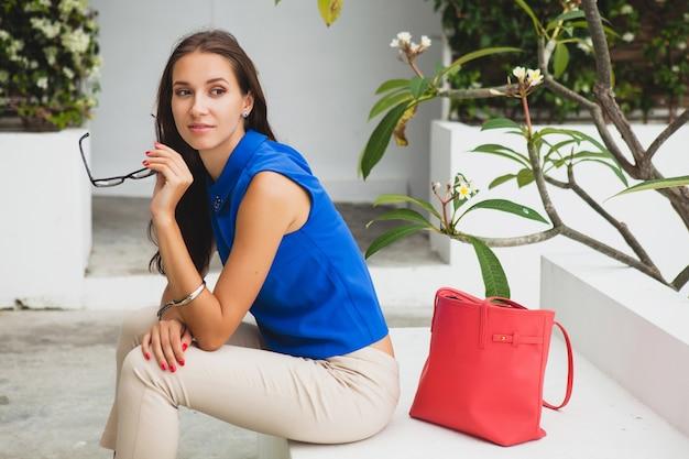 若いスタイリッシュな美しい女性、夏のファッショントレンド、青いブラウス、赤いバッグ、メガネ、トロピカルヴィラリゾート、休暇、軽薄