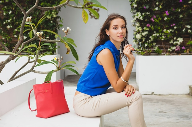 Young stylish beautiful woman, summer fashion trend, blue blouse, red bag, glasses, tropical villa resort, vacation, flirty