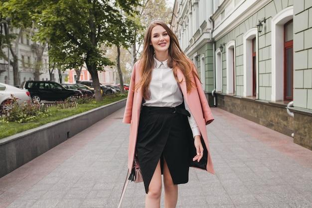 通りを歩いて、ピンクのコートを着ている若いスタイリッシュな美しい女性