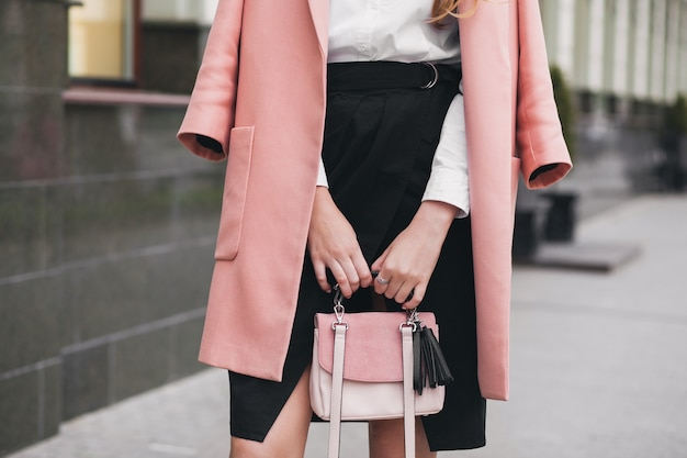 Young stylish beautiful woman walking in street, wearing pink coat, holding purse, black skirt, fashion outfit, autumn trend, accessories, hands close-up, details