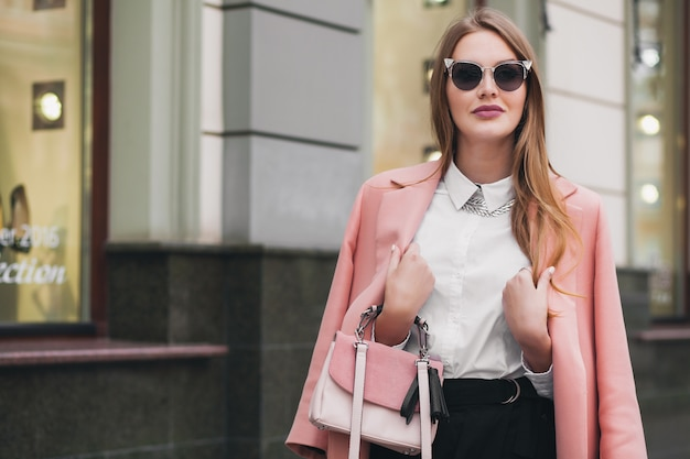 Young stylish beautiful woman walking in street, wearing pink coat
