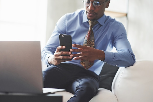 양복과 안경에 젊은 세련된 흑인 남자가 소파에 앉아있는 동안 전화를 들고 찾고