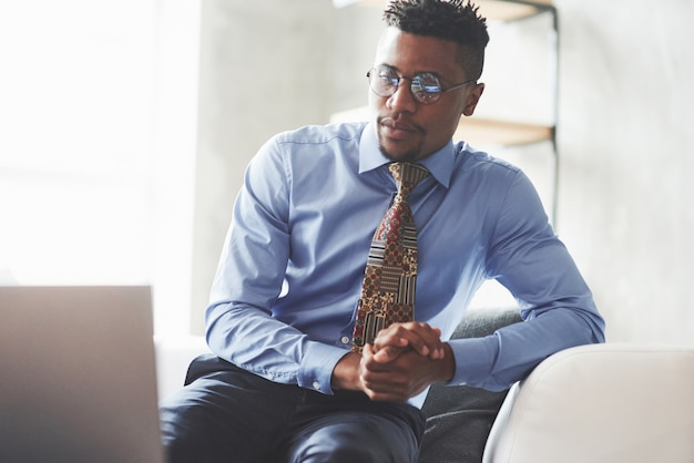 Young stylish black man in the suit and glasses sitting on the sofa and looking at a laptop
