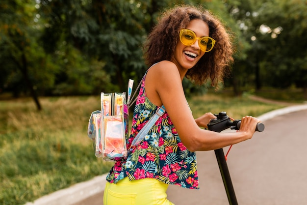 夏のファッションスタイル、カラフルなヒップスターの衣装、バックパックと黄色のサングラスを身に着けている電動キックスクーターに乗って公園で楽しんでいる若いスタイリッシュな黒人女性
