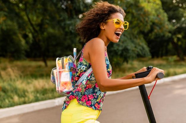 배낭과 노란색 선글라스를 착용, 여름 패션 스타일, 다채로운 힙 스터 복장에 전기 킥 스쿠터를 타고 공원에서 재미 젊은 세련된 흑인 여성