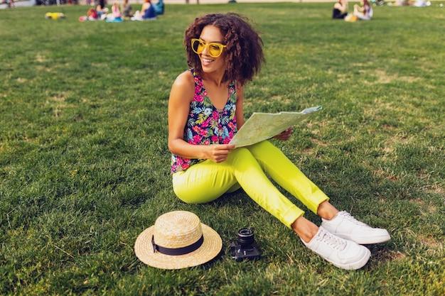 公園の夏のファッションスタイル、カラフルな流行に敏感な衣装、草の上に座って、地図と旅行者を楽しんでいる若いスタイリッシュな黒人女性