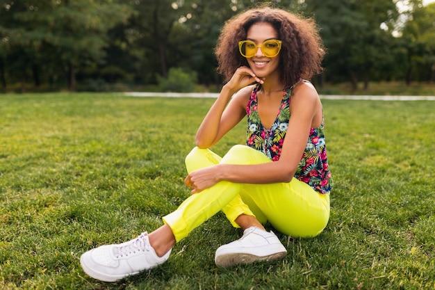 Молодая стильная темнокожая женщина веселится в парке летней моды, красочный хипстерский наряд, сидит на траве в желтых солнцезащитных очках и брюках, кроссовках