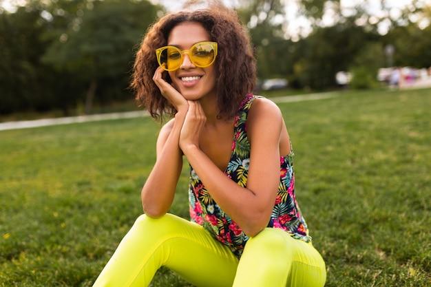 Молодая стильная темнокожая женщина веселится в парке в стиле летней моды, красочном хипстерском наряде, сидит на траве в желтых очках